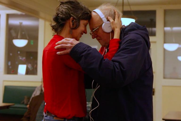 Woman in red shirt embracing elder man in blue sweatshirt wearing headphones